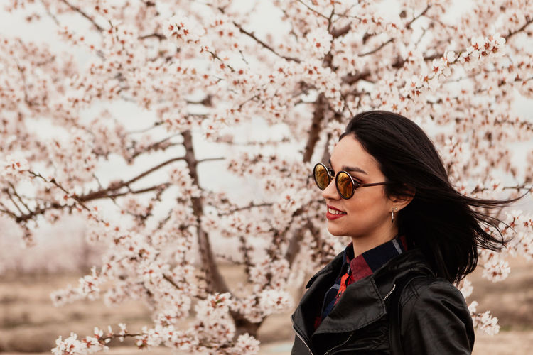 Low angle view of young woman with cherry blossom