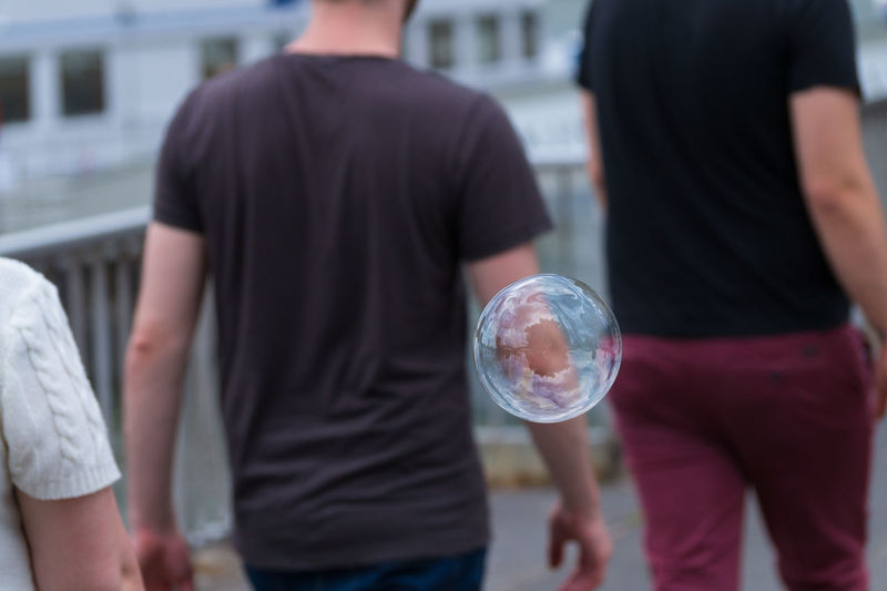 Close-up of bubble against men on street