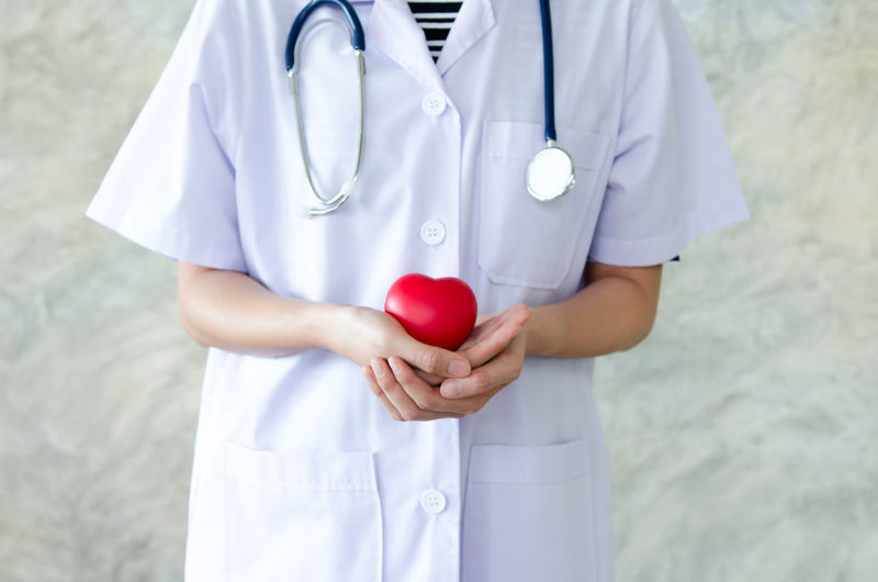Midsection Of Female Doctor Holding Red Heart Shape Against Wall