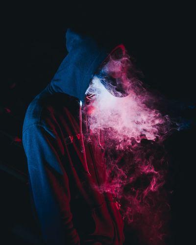 Man exhaling smoke while standing in darkroom