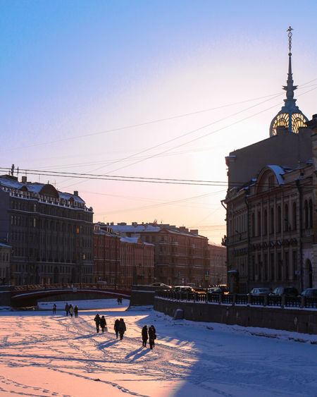 People on snow covered city against sky during sunset