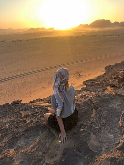 Rear view of woman sitting on rock at desert during sunset