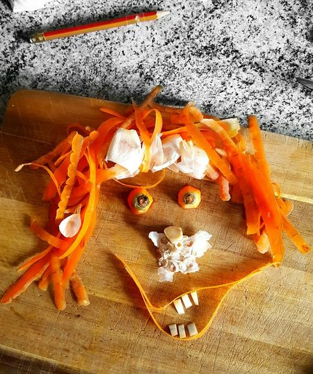 High Angle View Of Anthropomorphic Face Made From Carrot Peel And Garlic On Cutting Board