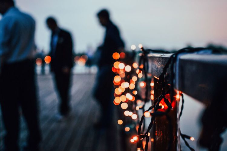 Close-up of lightings on railing with people in background
