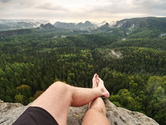 Big bloody callus on man's heel. closeup of man feet relax on rocky summit at edge. man enjoy view