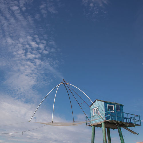 Low angle view of beach hut against blue sky