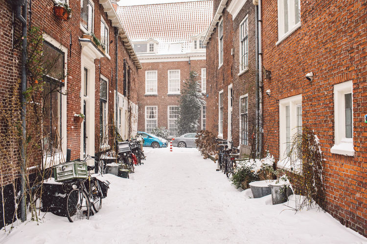 Street amidst houses and snow covered buildings in city