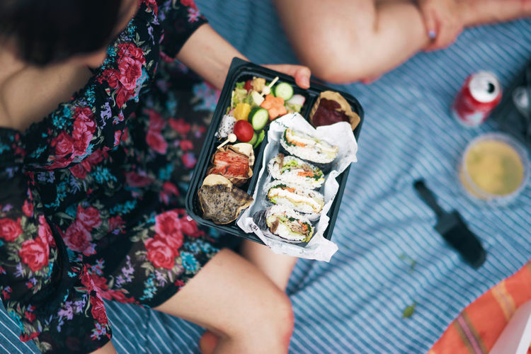 Cropped Image Of Woman Holding Sushi In Container