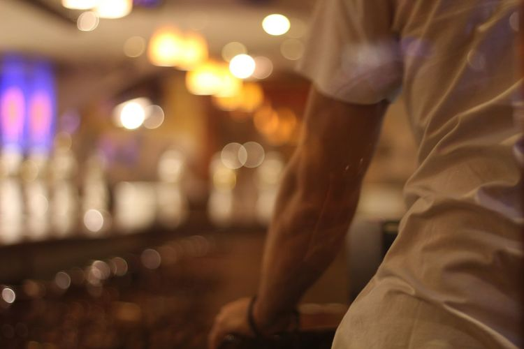 Midsection of bartender seen from glass window