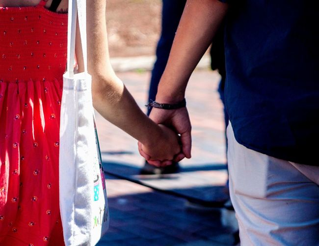 Midsection of couple holding hands while standing on street