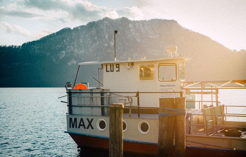 Boat moored on sea against mountain range