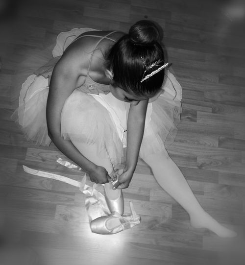 High Angle View Of Female Ballet Dancer Wearing Shoes While Sitting On Hardwood Floor