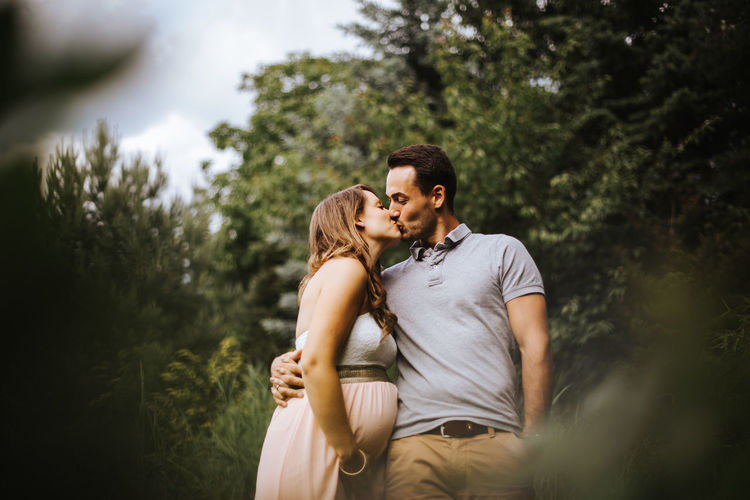 Low Angle View Of Couple Kissing While Standing Against Trees In Forest