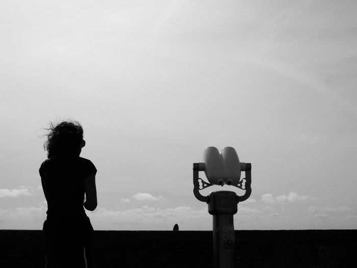 Silhouette of man photographing against sky