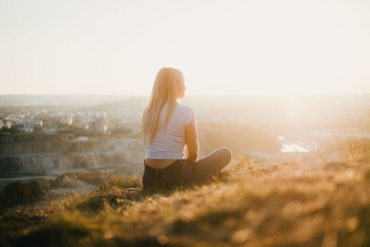 Woman sitting on land against clear sky