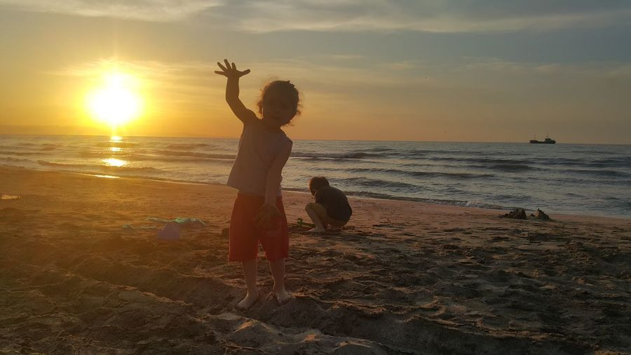 Children playing at beach against sky during sunset