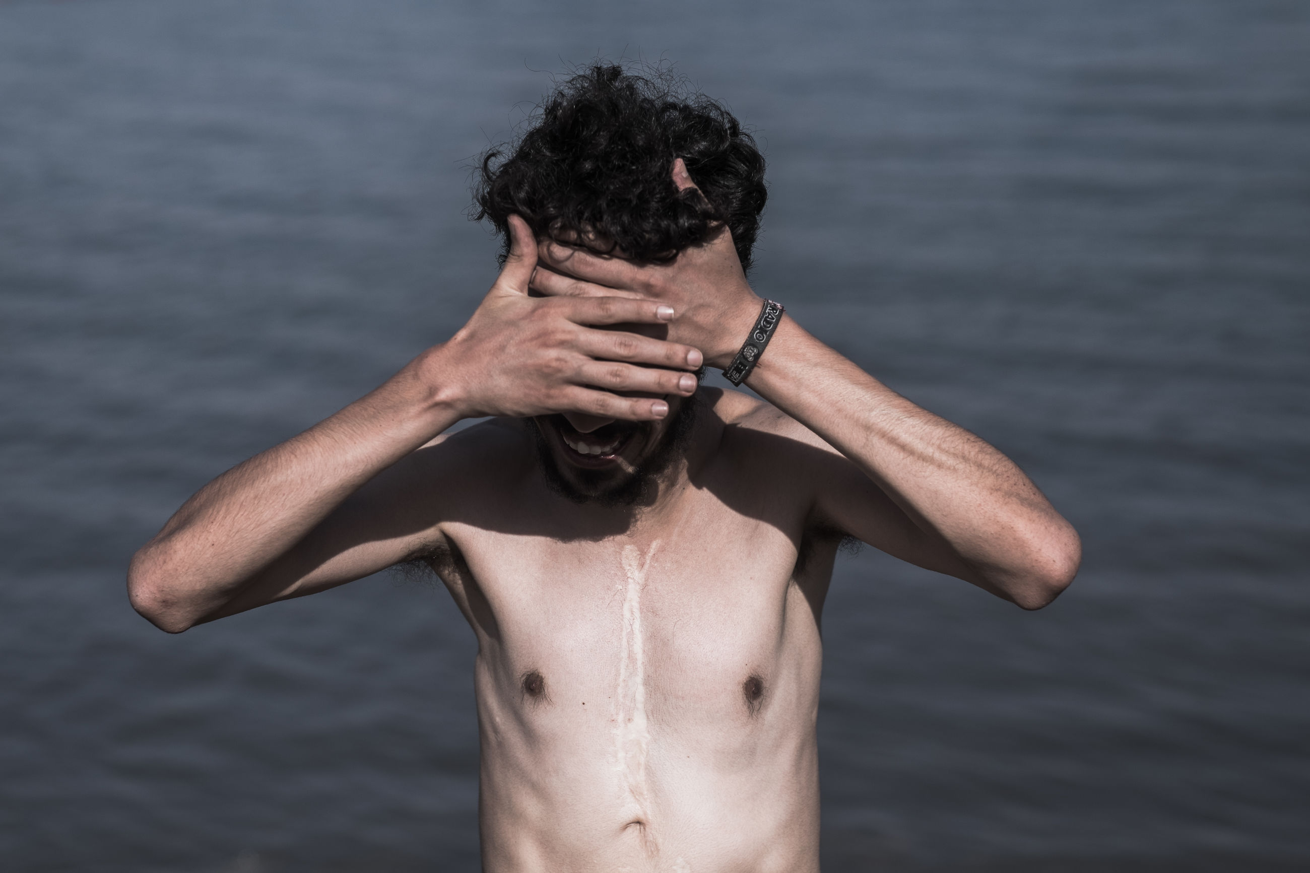 young adult, lifestyles, water, leisure activity, person, young men, shirtless, side view, three quarter length, holding, waterfront, front view, sea, sunglasses, vacations, focus on foreground, mid adult