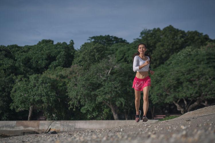 Full length of woman running on landscape against trees