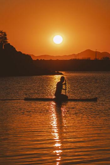 Silhouette man on sea against orange sky