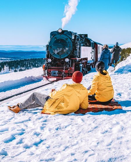 Couple sitting on snow covered land at railroad station against clear blue sky