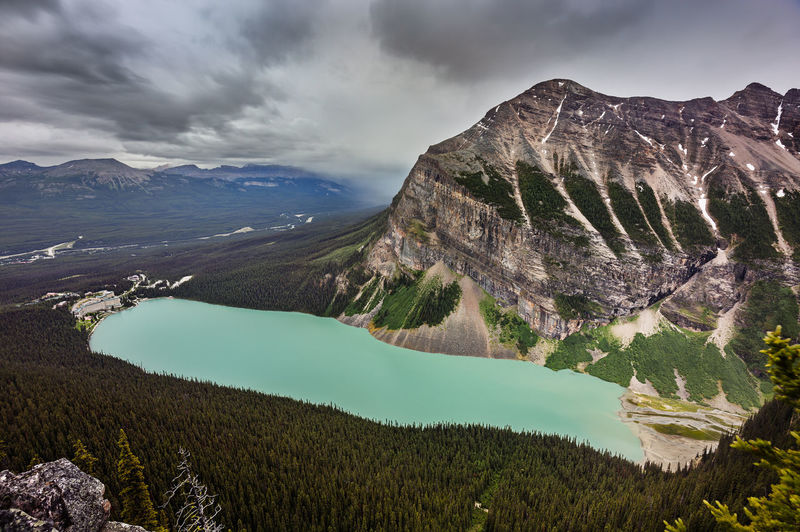 As I stood at the edge of the cliff | As I stood at the edge of the cliff of the Big Beehive, the sweeping Lake Louise view spread out before me. The regal Fairview Mountain towered at the foot of the world famous, glacier-fed lake as though it were watching over it. The 126-year-old stately chateau sat resolutely at one end of the lake as it always has as a hallmark of luxury. I'm sure it has seen it all. I saw the persistent rain clouds advancing fast up the valley as leaving it only tramped on in shower. It'll be here soon… Any minute now… Banff National Park, AB Adventure Alberta Banff  Banff National Park  Beauty In Nature Canada Château Fairview Mountain Lake Louise  Landscape Landscape Photography Mountain Mountain Range Mountains Mountains Are Calling Nature No People Outdoors Overcast Rain Clouds Sky The Big Beehive Travel Destinations Trees Wilderness