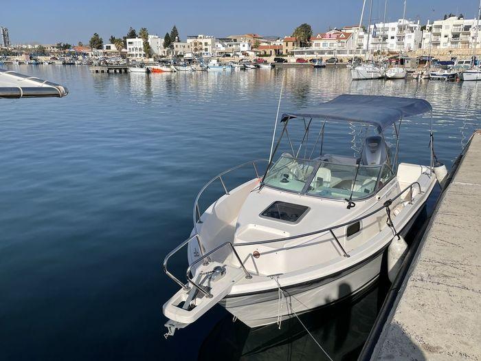 Sailboats moored at harbor in city
