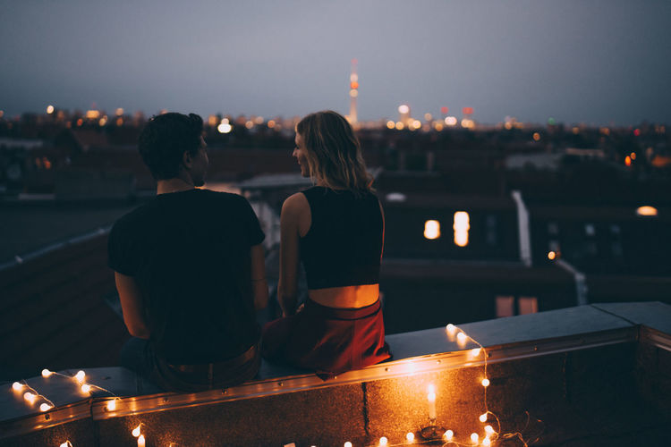 Rear view of couple walking on illuminated city against sky