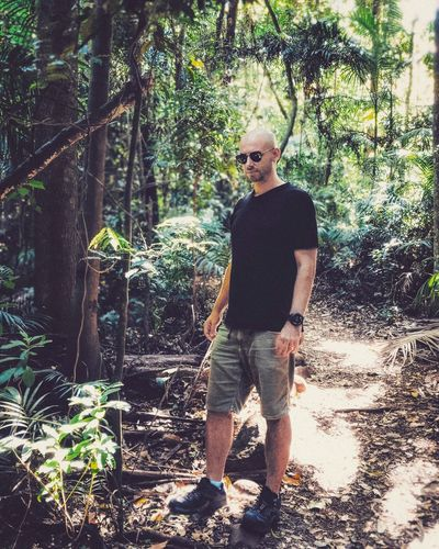 Full length of young man standing in forest