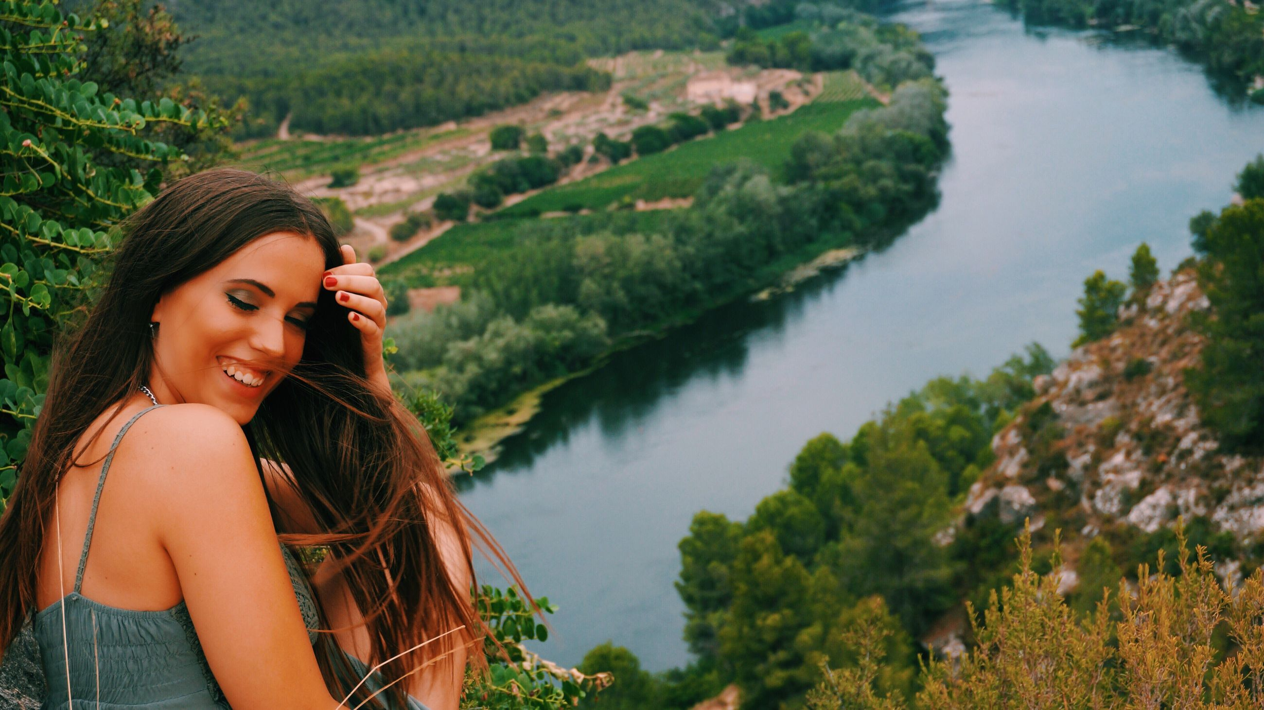 tree, lake, young adult, water, young women, long hair, leisure activity, lifestyles, casual clothing, scenics, tranquility, tourism, beauty, lakeshore, mountain, nature, beauty in nature, tranquil scene, looking at camera, black hair, vacations, person, green color