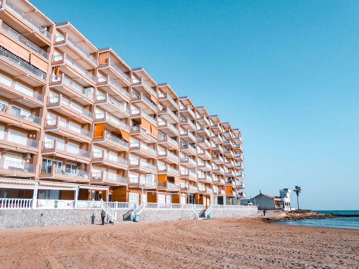 View of building by beach against clear blue sky