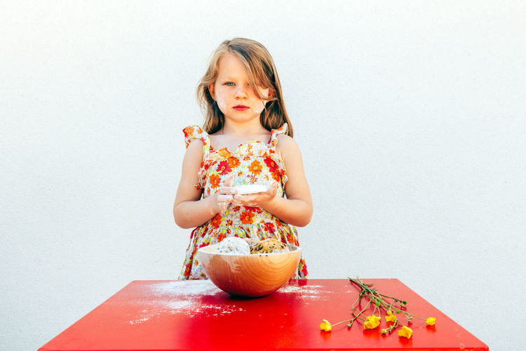 portrait of a little girl with a soiled face flour, isolated on white background, wearing a flower theme dress. A bowl with cookies and yellow flowers are on the table Portrait Kid Girl Soiled Face Flour Isolated White Background Flower Dress Springtime Summer Caucasian Cookie Cookies Baking Food Child Blond Hair Red Table Bowl Cute Biscuits Females Sneaky Sweet Calories Dessert Eat Temptation Childhood Female Cheerful Beauty Little Girl Cooking Sweet Food Indoors  Girls One Person Front View Women Studio Shot Copy Space Holding Lifestyles Wall - Building Feature Food And Drink Innocence Chef