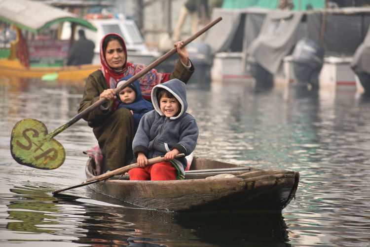 Woman With Children Oaring Canoe On Lake During Winter