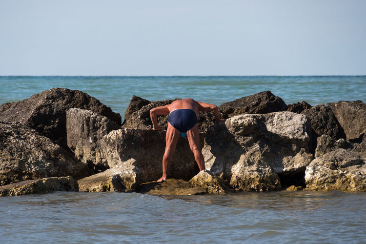 Rear view of man on rock by sea against clear sky