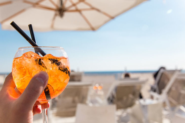 Close-up of hand holding drink at beach