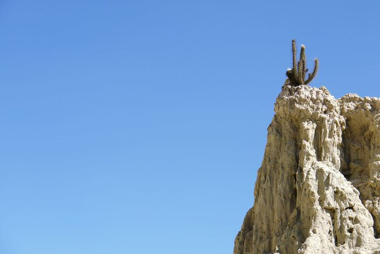 Low angle view of clear blue sky and cliff