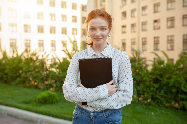 Woman holding book while standing in campus