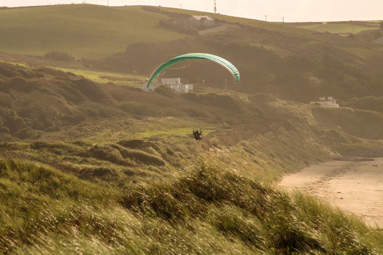 Person paragliding over land