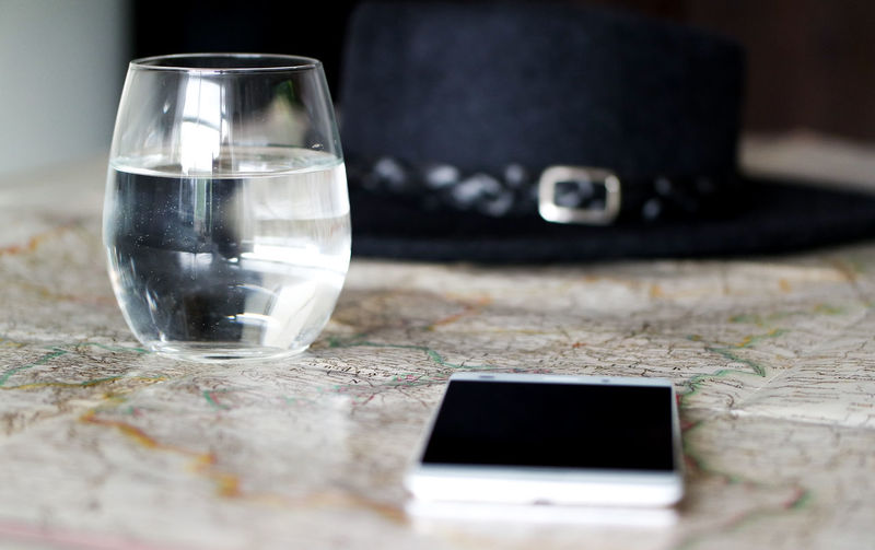 Close-up of smart phone with drinking glass on map