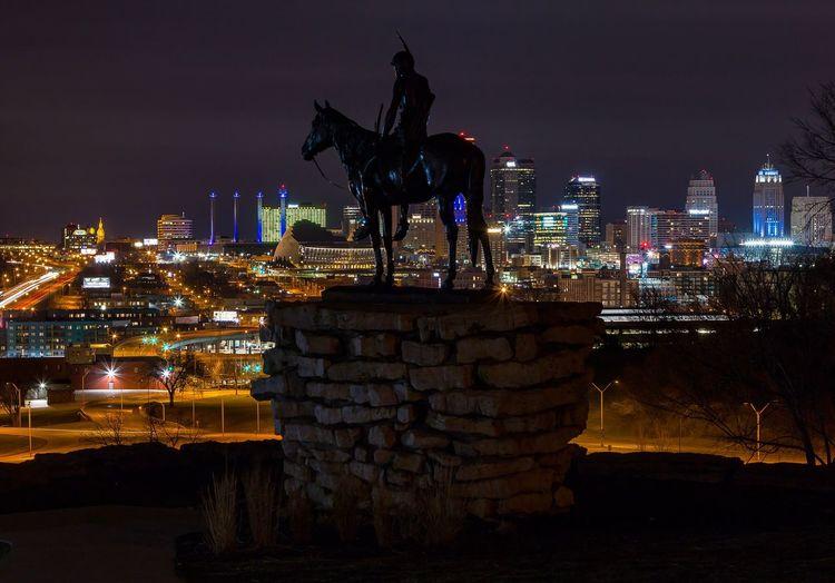 Statue against illuminated city at night