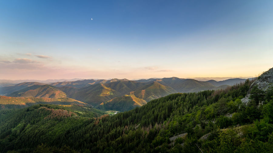 The moon watches from above as the last rays of the summer sun gild the soft forms of the Rhodope mountains in the south of Bulgaria Blue Hour Rhodopes Beauty In Nature Bulgaria Landscape Mountain Mountain Range Nature No People Outdoors Sky Summer Sunset