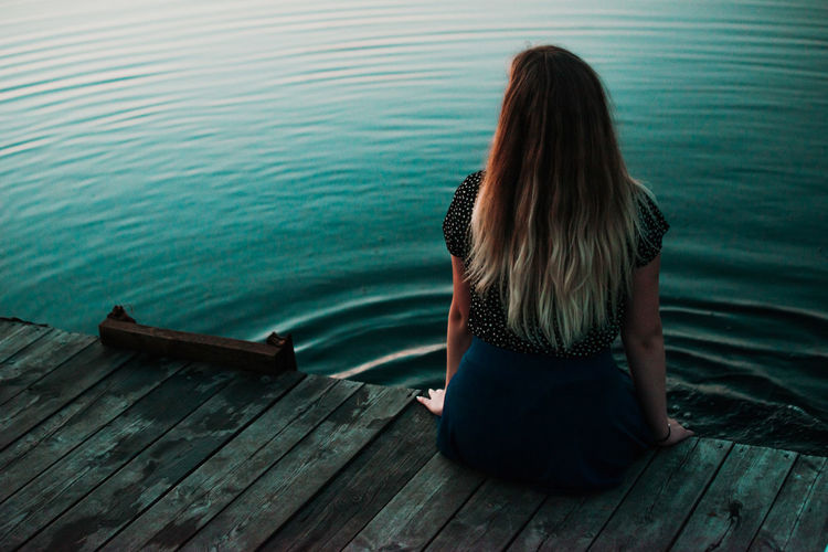 lonely girl sitting in fornt of bog lake in the evening Estonia Adult Bog Contemplation Day Full Length Grainy Hair Hairstyle Lake Leisure Activity Lifestyles Long Hair Nature Night One Person Outdoors Pier Real People Rear View Sitting Water Women Wood Wood - Material