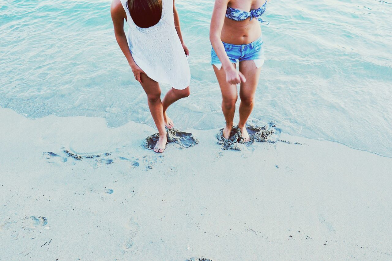 Low section of young women standing on shore at beach