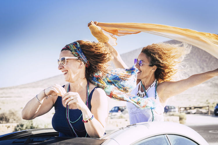 Couple of middle age caucasian woman cheerful and laughing enjoying the travel and the vacation with convertible car and playing with the wind for freedom lifestyle concept Glasses Transportation Sunglasses Smiling Happiness Mode Of Transportation Car Fashion Sunlight Young Adult Lifestyles Motor Vehicle Emotion Leisure Activity Fun Adult Day Enjoyment Young Women Road Trip Outdoors Mother Freedom Horizon Over Water Landscape Horizontal Format Cheerful Couple Two People On The Beach Caucasian Casual Clothing Hippie Bonding 40-44 Years Tropical