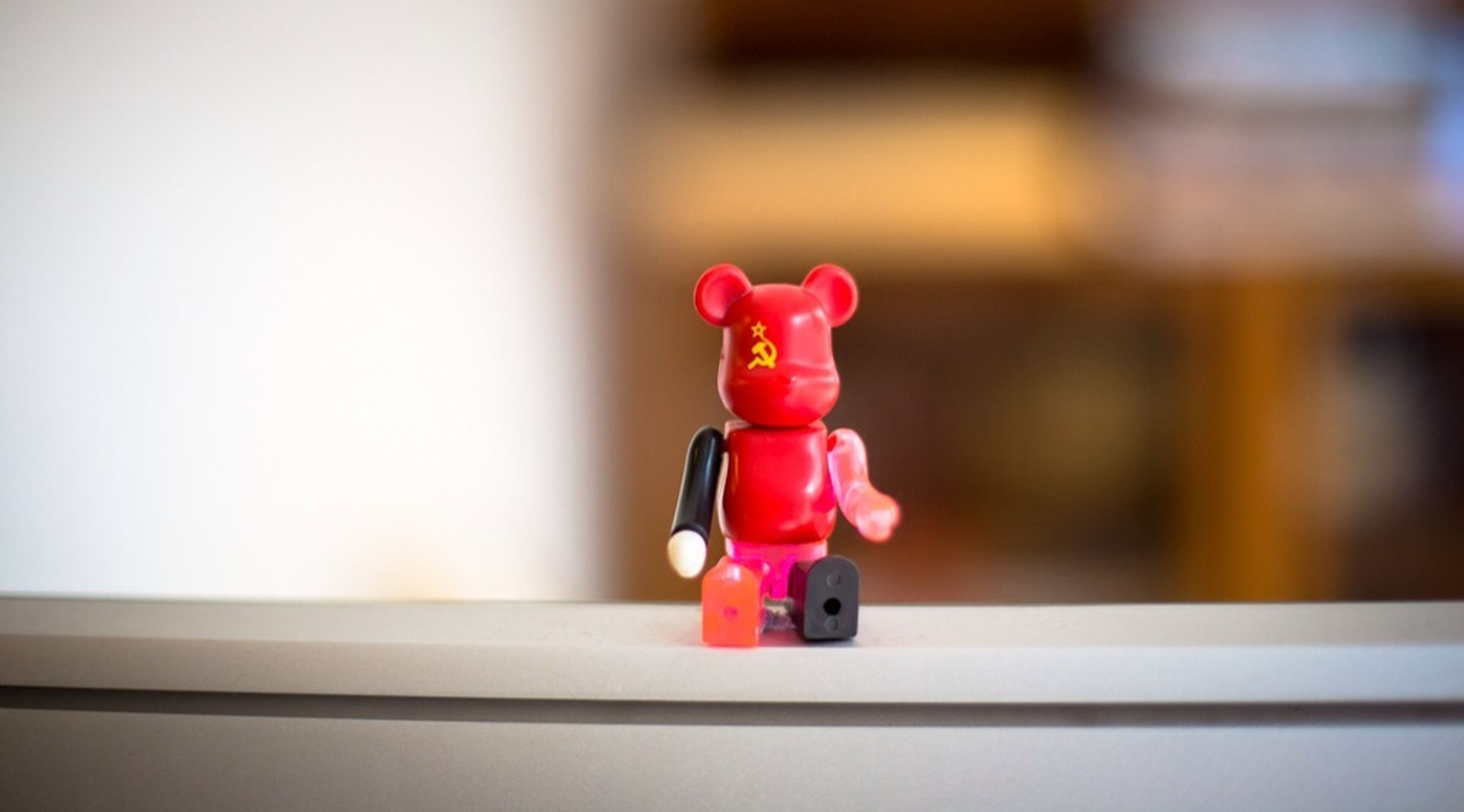 indoors, human representation, art and craft, art, focus on foreground, creativity, close-up, statue, figurine, sculpture, red, animal representation, still life, toy, no people, wall - building feature, selective focus, home interior