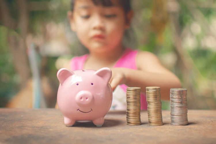 Close-up of a girl with piggy bank and stack of coins