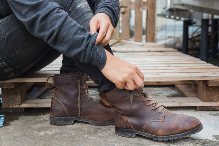 Bench Body Part Boot Casual Clothing Day Focus On Foreground Human Body Part Human Foot Human Leg Jeans Leather Lifestyles Low Section Men One Person Outdoors Real People Relaxation Seat Shoe Sitting Wood - Material