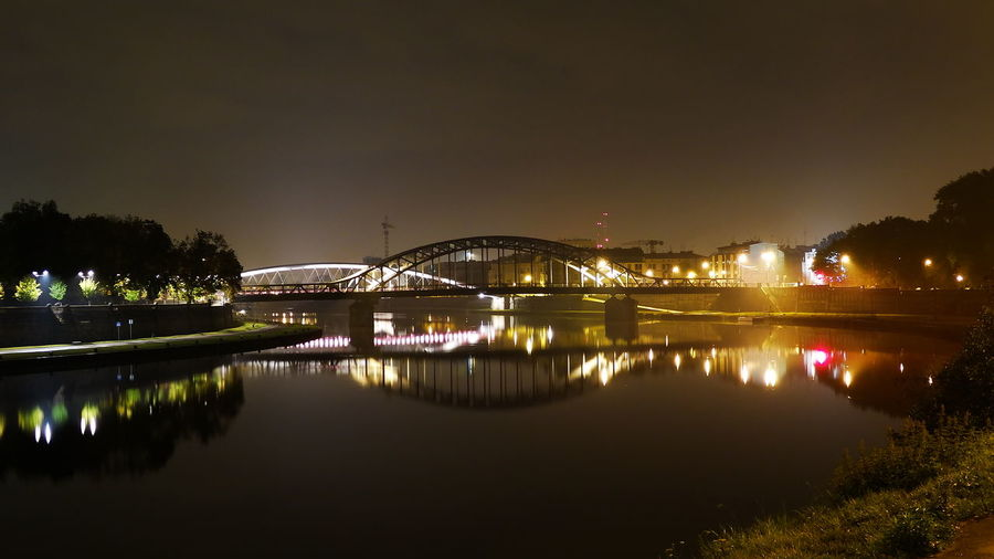Reflection Of Illuminated Bridge In River Against Sky At Night