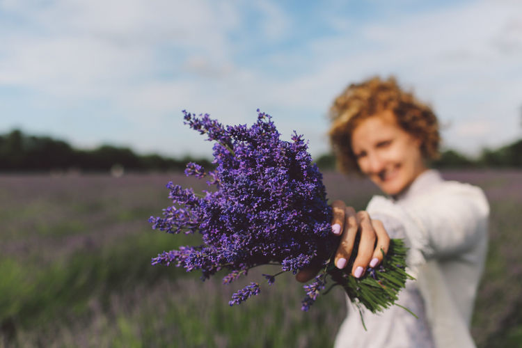 Close-Up Of Woman Holding Lavender Flowers On Field Against Sky