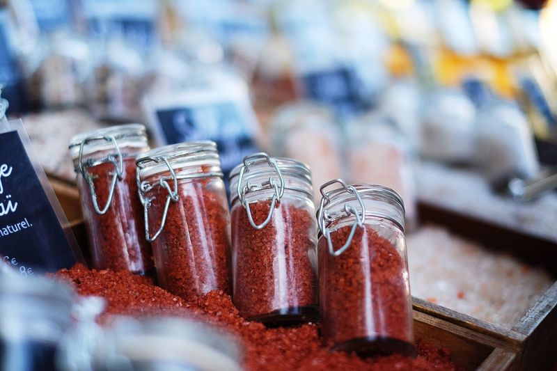 Close-up of alaea salts in glass containers for sale