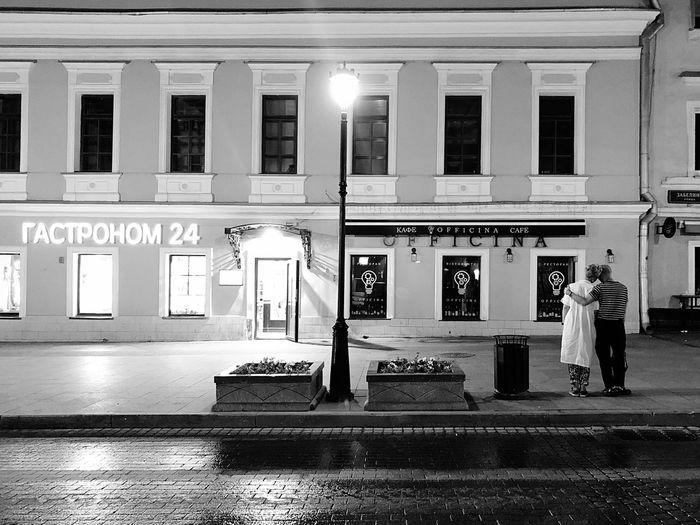 Man walking on illuminated street in city at night